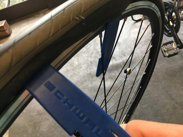 自転車タイヤレバー1本を引っ掛けて、もう1本でタイヤを外していく
