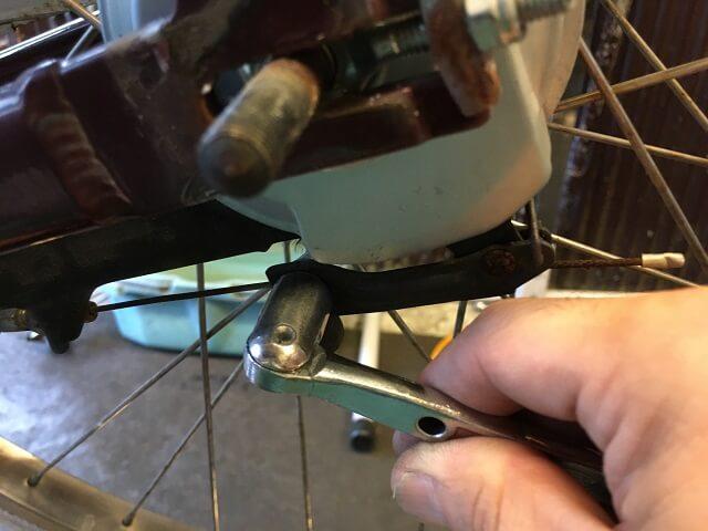 後輪ブレーキケーブル固定ナットを緩める