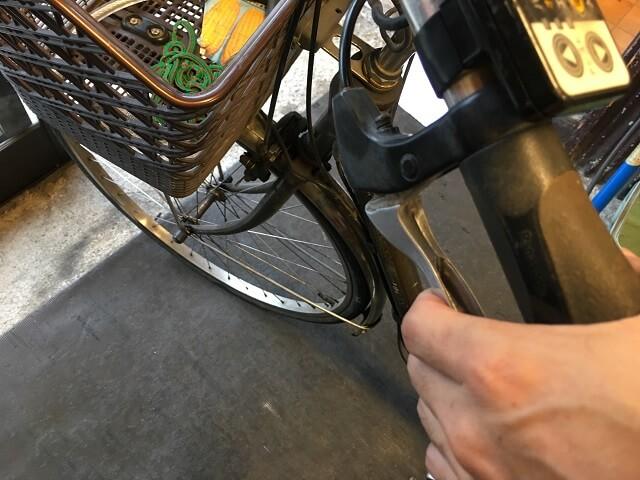 後輪ブレーキレバーを握りブレーキ調整確認作業をする