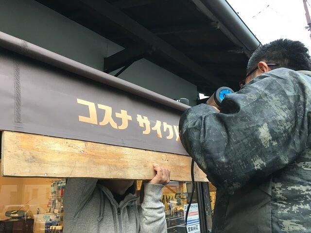 コスナサイクル日よけテントにロゴシール貼る作業