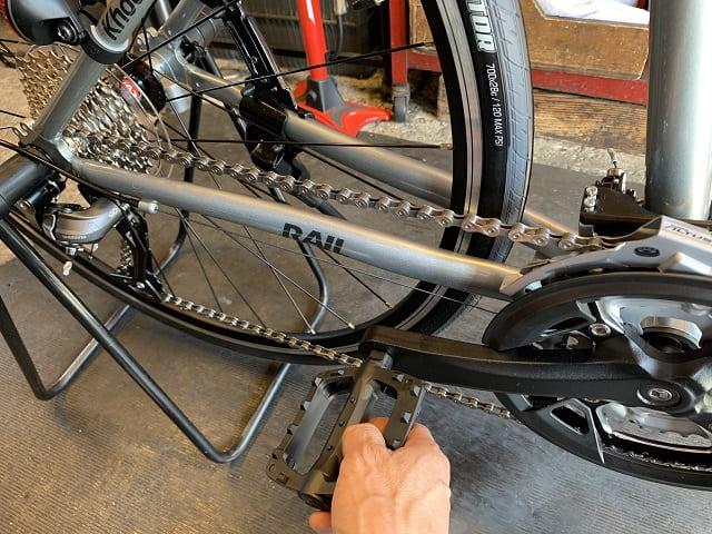 自転車組立作業クロスバイクのペダルを回して変速微調整