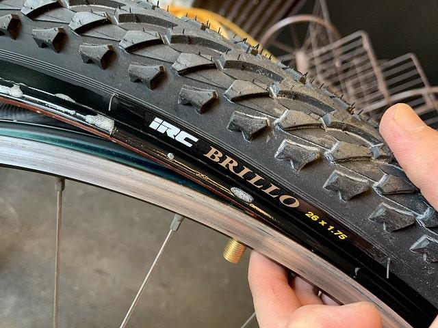 マウンテンバイクタイヤ交換作業タイヤのゴロ位置を合わせてはめていく