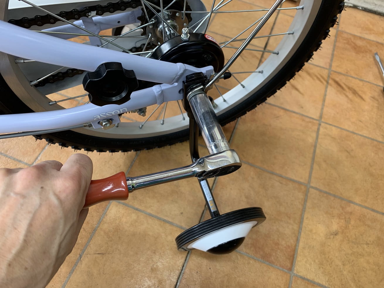 子供自転車補助取り外しのためナットを工具で緩める